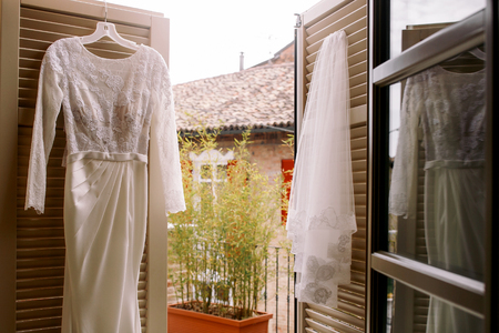 Classy wedding gown and veil hang on the doors to tha balcony
