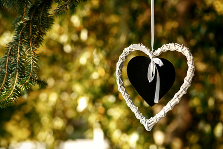 Black heart put into the white heart hang from the tree
