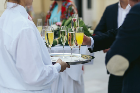 Guests in black suits take glasses of champagne from a tray