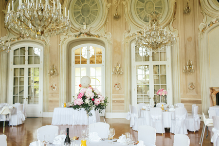 Magnificent crystal chandelier hang over the white dinner tables