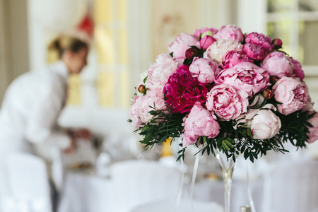 Picture of pink bouquet standing on the dinner table in restaurant hall Stock Photo