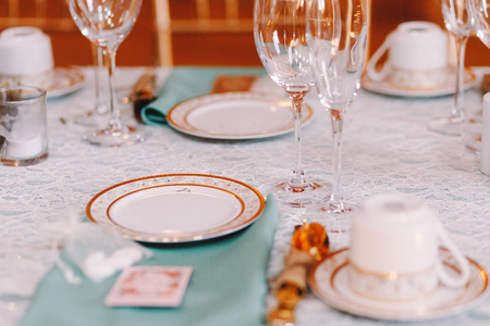 ceiling plate: White crockery with golden design stand on the blue tablecloth
