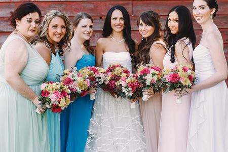 Attractive bridesmaids surround a pretty bride while posing before a wooden hangar Stockfoto