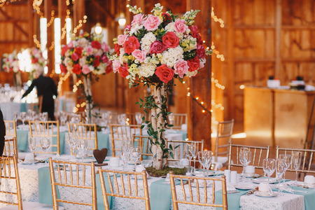 ceiling plate: Pink bouquets stand on the dinner tables in wooden hangar