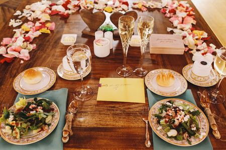 ceiling plate: Plates with salads and buns stand on the dinner table prepared for wedding couple