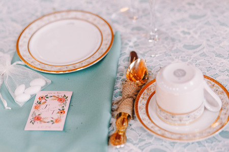 ceiling plate: Golden cutlery tied with a rope stand behind white crockery