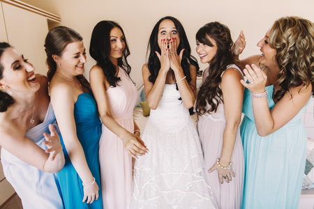 shoked: Shoked bride closes her mouth with her palms standing between bridesmaids