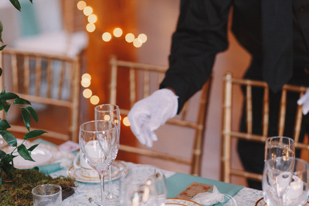 ceiling plate: Waiter in white gloves adjusts glassware on the dinner table