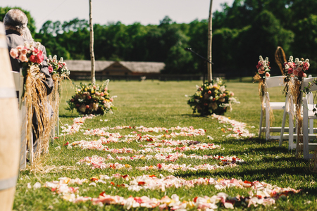 Pink and yellow petals cover the green path to wedding altar Stock Photo