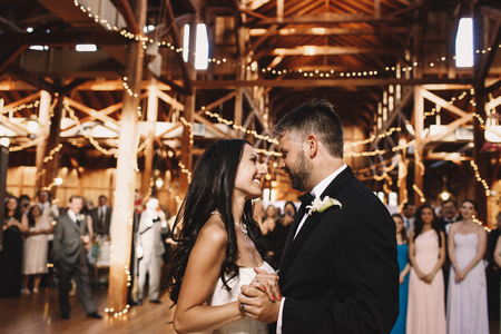 Happy newlyweds admire each other while dancing in the wooden hall Editorial