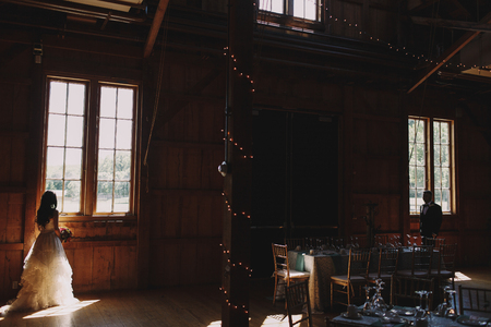 Bride and groom stand apart in a dark hangar decorated with garlands for a wedding