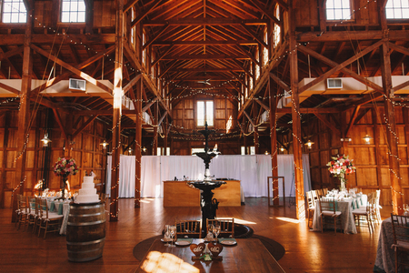 ceiling plate: Black fountain stands in the middle of wooden hangar prepared for a wedding dinner