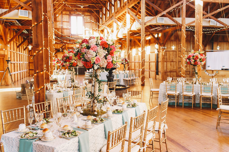 Shining hangar full of light garlands and festive served dinner tables