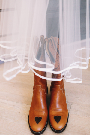 Red leather boots stand under the veil