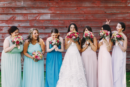 Bride and bridesmaids grimace while hiding their faces behind their bouquets Stock Photo