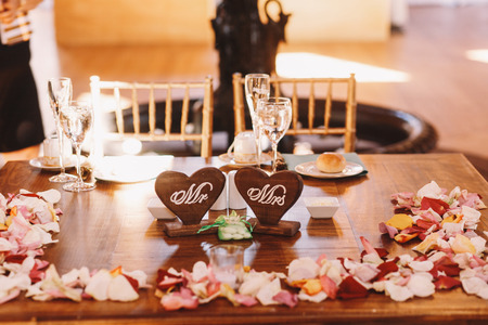 ceiling plate: Wooden table covered with petals ant decorated with woodeh hearts Mr and Mrs Stock Photo