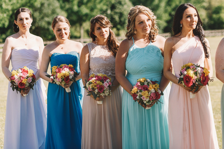 Smiling bridesmaids in pastel dress stand in a row behind the bride