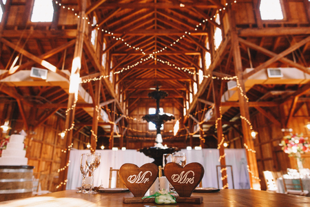 Sparkling light garlands hang from the ceiling in a wooden hangar prepared for a wedding Stock Photo