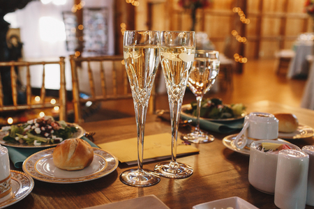 ceiling plate: Crystal flutes with champagne stand on the wooden dinner tables