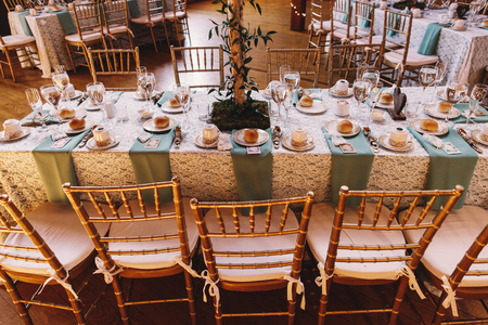 ceiling plate: Bamboo chairs stand at the dinner table decorated with blue serviettes