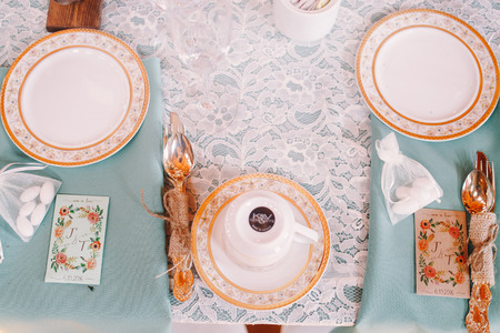 Look from above on a cup standing turned upside down on the white plate with golden design