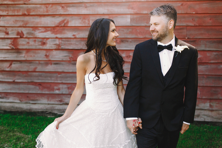 Happy newlyweds walk holding each other hands tightly from the wooden wall