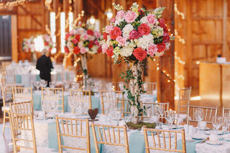 ceiling plate: Gorgeous pink bouquet stands over the dinner table covered with blue cloth Stock Photo