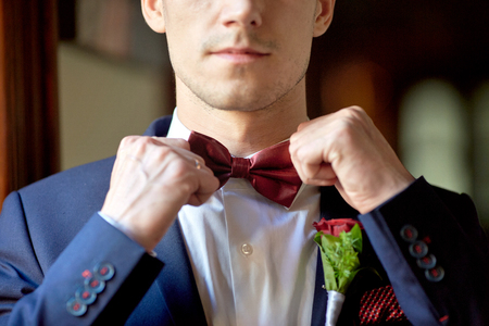 Groom adjusts a wine bow tie on his white shirt