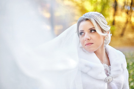 Blurred picture of a bride in fur coat looking over her shoulder while wind blows a veil