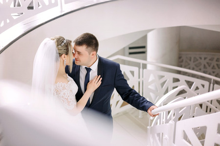 Kissing wedding couple poses on white spiral stairs