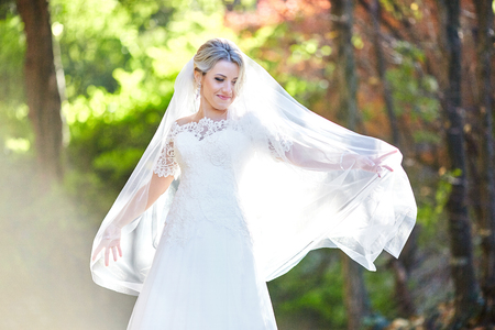 Bride looks over her shoulder covered with veil while posing in the wood