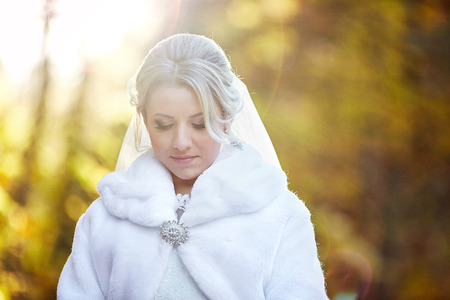 Autumn sun shines over a gorgeous bride in white fur coat Stock Photo