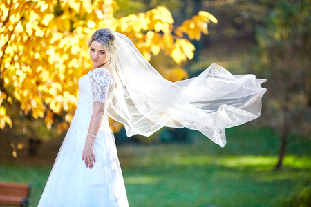 Wind blows brides veil while she poses in the autumn park