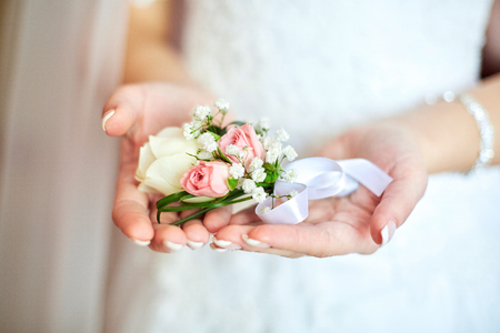 Tender boutonniere made of white and pink roses lies on brides palms