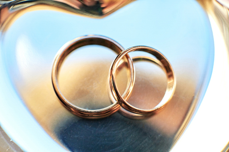 Closeup of wedding rings lying on the golden plate Stock Photo