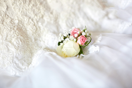 Gorgeous boutonniere lies over the wedding dress