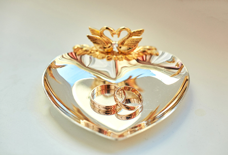 Wedding rings lie on the beautiful golden plate decorated with swans