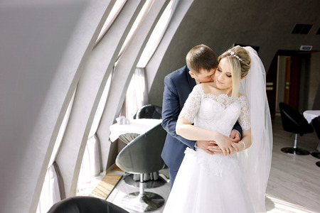 Groom kisses brides neck while standing before the panoramic windows Stock Photo