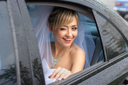Bride smiles while sitting in the car during the rain