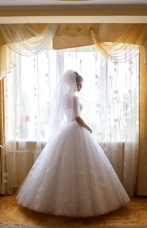 Thoughtful bride in magnificent dress stands before the beige curtains