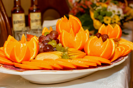 Sliced oranges and grapes lie on the serving dish