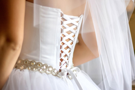 Look from behind at delicate brides back put in the silk corset Stock Photo