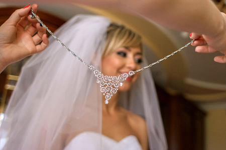 Look from the sparkling crystal necklace at a gorgeous bride standing in the room