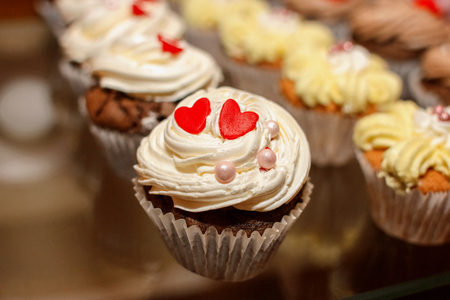 Closeup of cupcake decorated with red hearts and glaze pearls Stock Photo