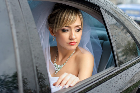 Thoughtful bride looks through the window of wet car