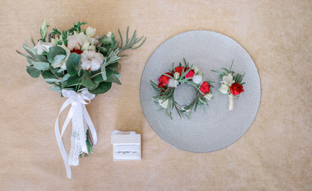 Little wreathe, boutonniere and wedding bouquet made of roses and white flowers