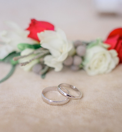 Silver wedding rings lie before boutonnieres made of red and white flowers Stockfoto
