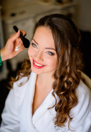 Bride smiles while sitting in white robe during make up