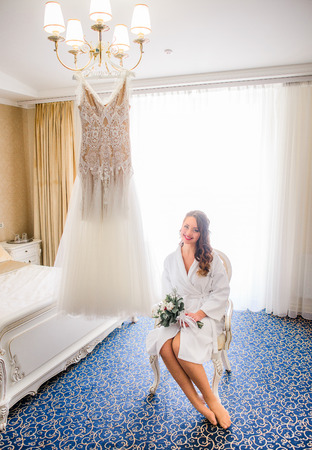 Happy bride sits before shining wedding dress which hangs on the chandelier