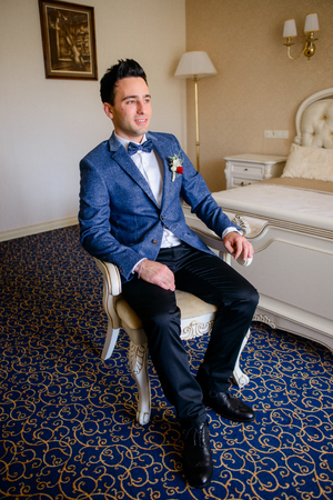 Confident groom in blue suit sits on the chair in rich hotel room